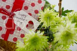 Gift box and bunch of yellow flowers in wicker basket with happy mothers day tag