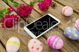 Painted Easter eggs, flowers and mobile phone on wooden surface