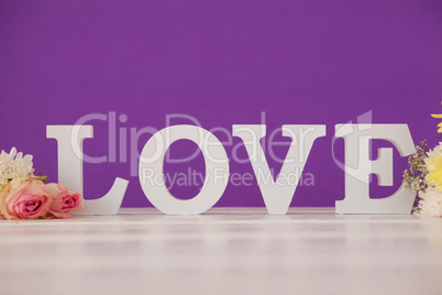 Flowers with alphabets forming love on table