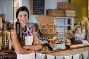 Portrait of smiling female staff standing with arms crossed at bakery shop