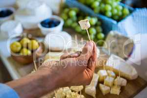 Staff showing a sample of cheese to customer at counter