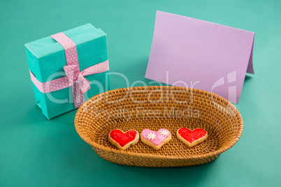 Gift box, heart shape cookies and blank card against green background