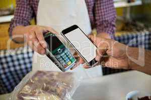 Mid section of man paying through nfc technology at counter