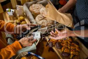 Customer paying bill by cash at bread counter