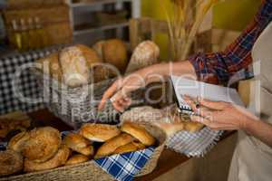 Female staff maintaining stock record at bread counter