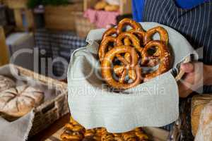 Mid section of staff holding wicker basket of pretzel breads at counter
