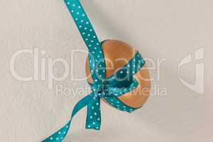 Golden easter egg tied with blue ribbon