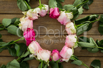 Pink roses arranged in round shape on wooden plank