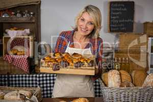Portrait of smiling female staff holding tray of sweet food at bread counter