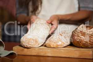 Mid-section of woman holding bread at counter