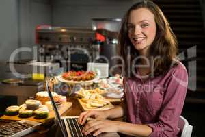 Woman using laptop at bakery counter in market