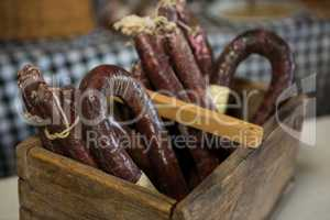 Sausages in wooden basket at counter in market