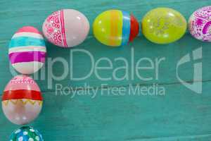 Painted Easter eggs arranged on wooden plank