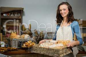 Portrait of female staff holding a basket of bread