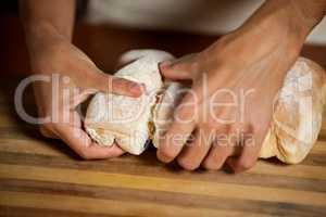Male staff tearing a bun in bakery shop
