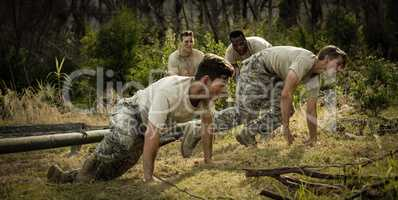 Soldiers crawling under the net during obstacle course