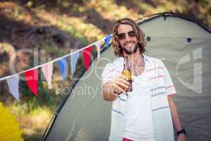 Portrait of man showing beer bottle at campsite