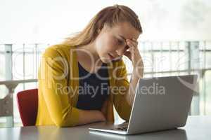 Sad schoolgirl looking at laptop in library