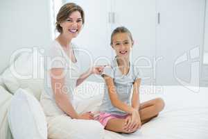 Smiling mother combing daughters hair on bed in bedroom at home