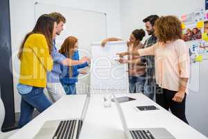 Executives discussing over flip chart board in conference room meeting