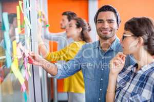 Portrait of smiling executives reading sticky notes on glass wall