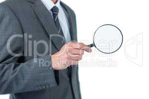 Mid section of businessman holding magnifying glass