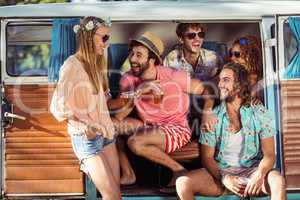 Group of happy friends sitting in campervan and drinking beer