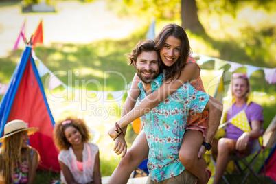 Man carrying woman on piggyback at campsite