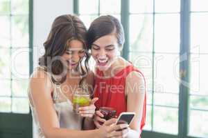 Friends with cocktail glasses while using mobile phone