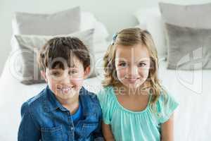 Portrait of smiling siblings sitting on sofa in living room