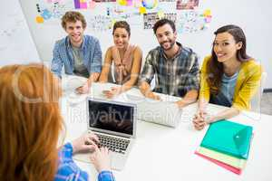 Executive discussing over laptop with her colleagues during meeting