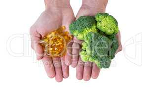 Close-up of hands holding broccoli and vitamin pills