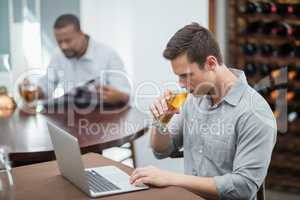 Handsome man drinking beer while using laptop
