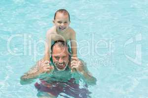 Portrait of father and son in swimming pool