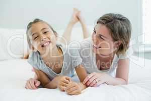 Smiling mother embracing her daughter while lying on bed in bedroom