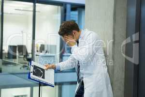 Upset male doctor standing near corridor