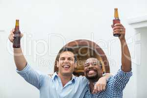 Friends cheering while watching football match