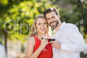 Happy couple holding wine glasses in the park