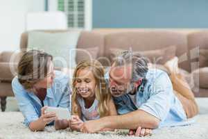 Family taking selfie from mobile phone while lying together on carpet in living room