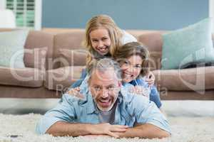 Portrait of happy family lying heaped on carpet in living room