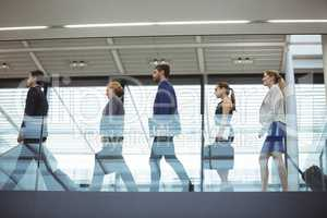 Business executives with trolley bag walking in the corridor