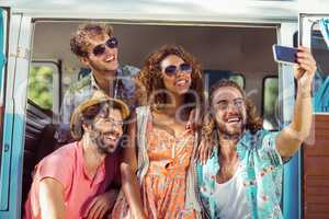 Group of happy friend taking a selfie in campervan