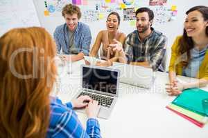 Colleagues discussing over laptop with executive during meeting