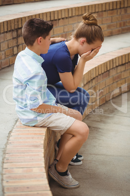 Schoolboy consoling her sad friend on steps in campus