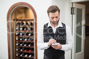 Male waiter taking down order