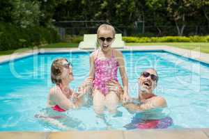 Happy parents and daughter having fun in pool