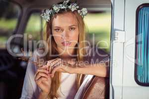 Portrait of woman with flower wreath sitting in campervan