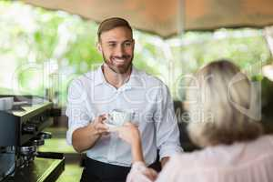 Waiter giving coffee to customer