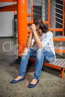 Sad female executive sitting on staircase