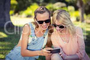 Woman showing mobile phone to her friend
